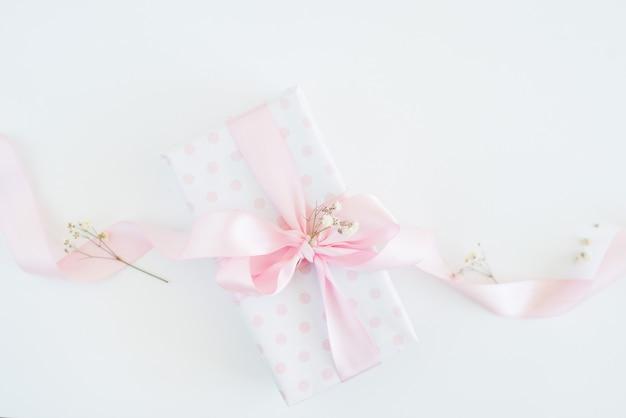ギフトボックス水玉紙、ピンクの弓、小さな花。女性の日