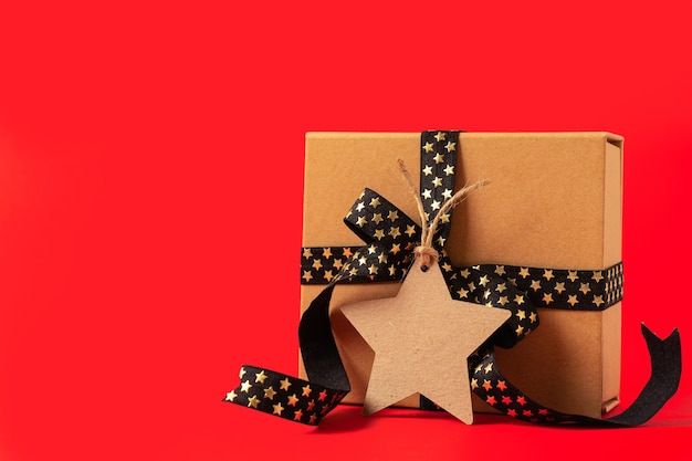 Gift box or present box with empty mock up tag black golden ribbon on red background