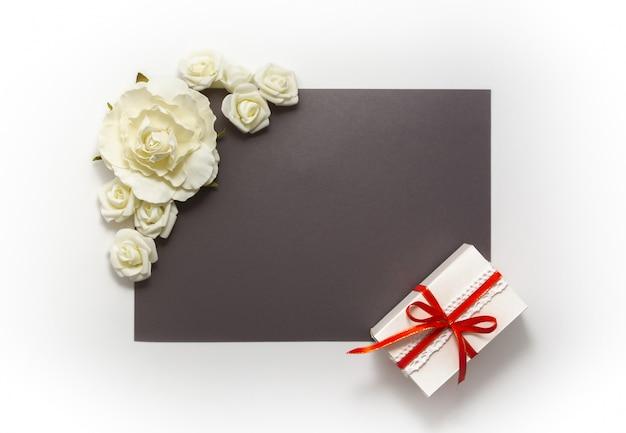 ギフトボックスプレゼント装飾フラットレイ。ギフト赤いリボン白い花のトップビュー。