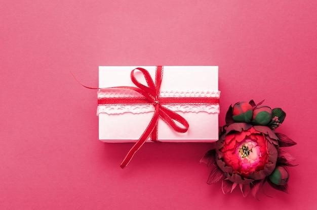 ギフトボックスプレゼント装飾フラットレイ。白いギフトリボンピンクの花のトップビュー。