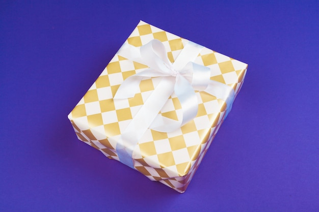 Gift box on purple background top view