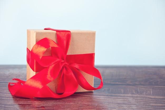 Подарочная коробка красный лук на деревянный стол. скопируйте пространство.