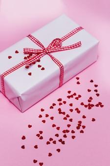 ギフトボックス、赤い紙吹雪、ピンクの背景にキラキラ。休日、お祭りの背景。