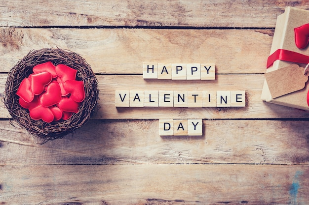 Gift box and red heart in nest with wooden text happy valentine day on wood table background.