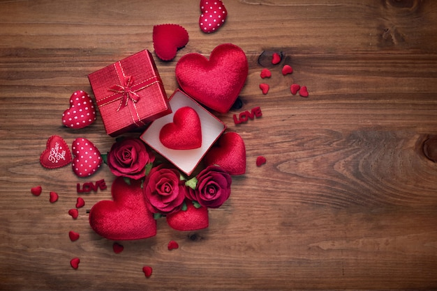 Gift box and red heart rose on wood background with copy space for love wedding or valentines day.