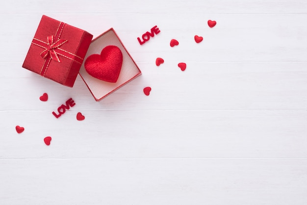 Gift box and red heart on white wood background with copy space for love wedding or valentines day.