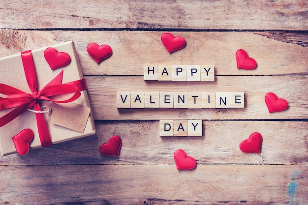 Gift box and red heart with wooden text happy valentine day on wood table background.