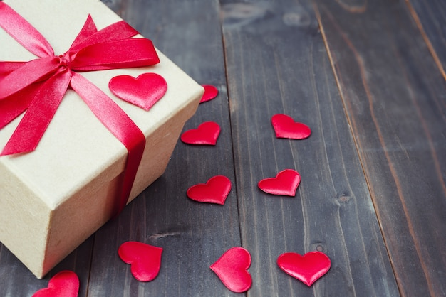 Gift box and red heart on wooden table background with copy space,