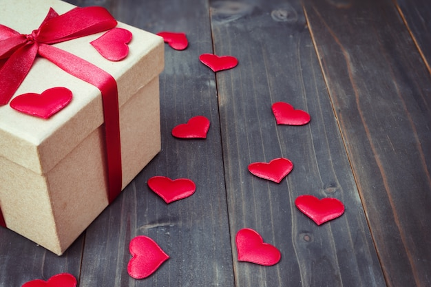 Gift box and red heart on wooden table background with copy space.