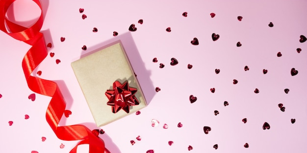 Gift box and red satin ribbon on the side on a pink background. little red hearts are scattered. free space for text. gift concept, holidays, love, valentine's day.
