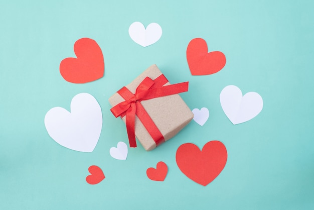 Gift box, red and white hearts on blue pastel background. valentine's day or wedding ceremony concept
