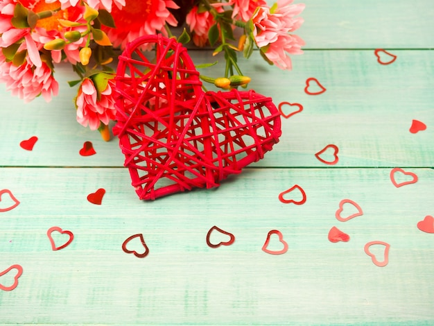 Gift box and red wicker heart on a blue wooden