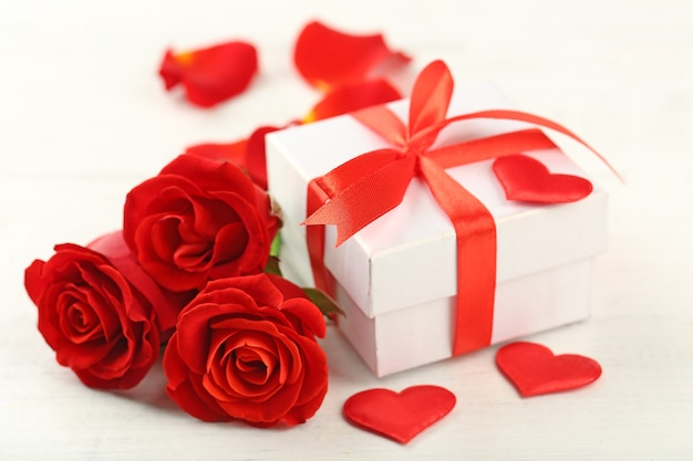 Gift box, rose flowers and decorative hearts on light wooden