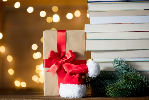 Gift box, santa claus hat and pile of books