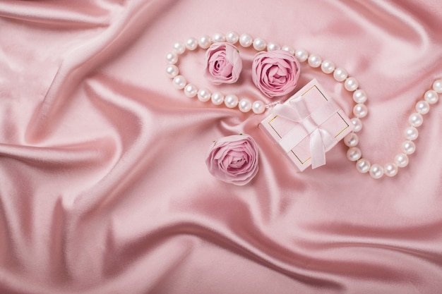 A gift box on a satin background is decorated with flowers and pearls