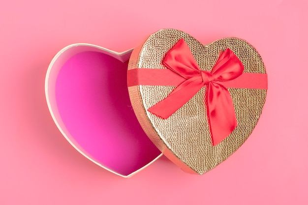 Gift box in the shape of a heart on a pink background. happy valentine's day concept.