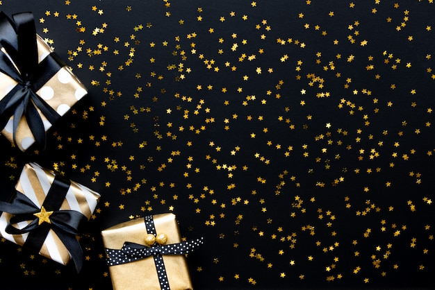 Gift box over star shaped golden sequins on a black background.