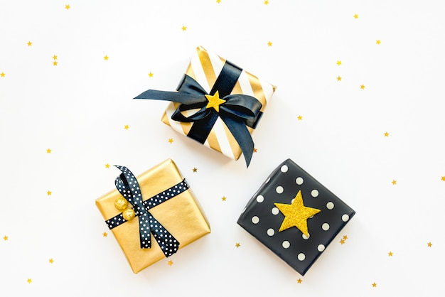 Gift box over star shaped golden sequins on a white background.