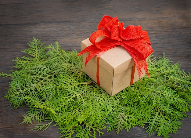 Gift box on thuja branches on wooden background