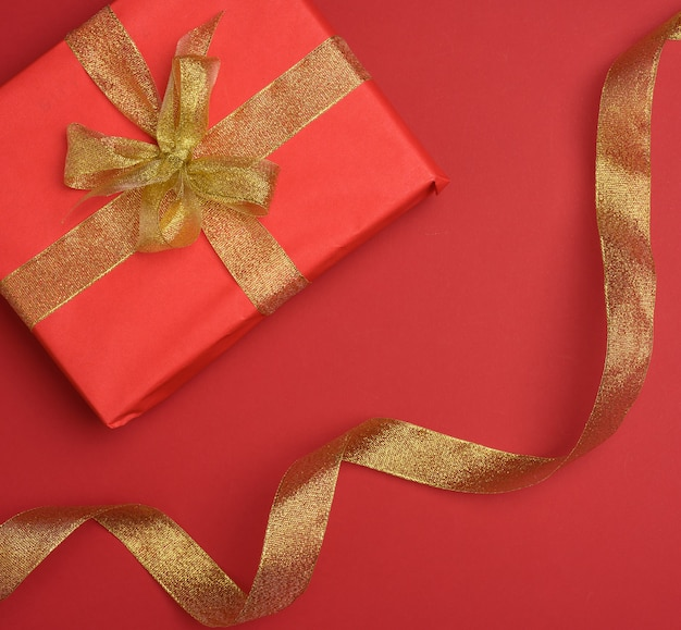 Gift box tied with silk ribbon on a red background, top view. festive backdrop