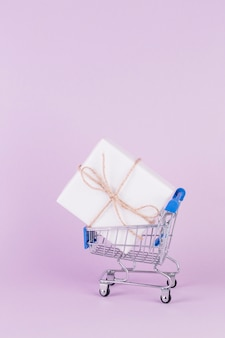 Gift box tied with string in shopping cart on pink background