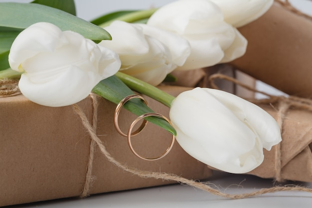 Gift box and tulips bouquet on white surface