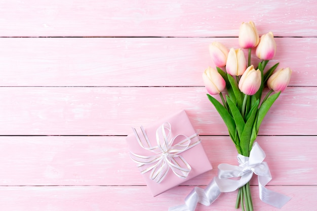 Gift box and tulips with ribbon on wooden.
