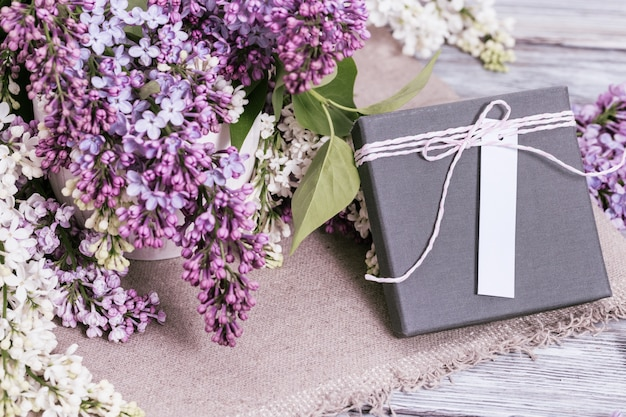 Gift box and violet lilac flowers on table.