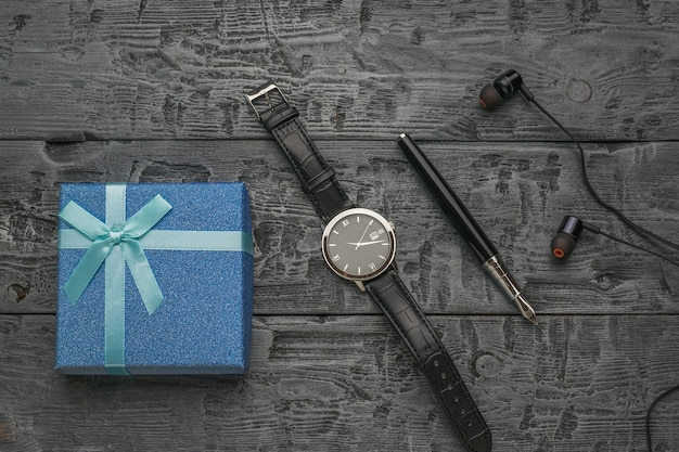 나무 배경에 선물 상자, 시계, 만년필, 헤드폰. 남자를 위한 선물.