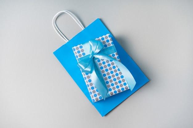Подарочная коробка с синим бантом на сером фоне на синем бумажном пакете. праздничный подарок
