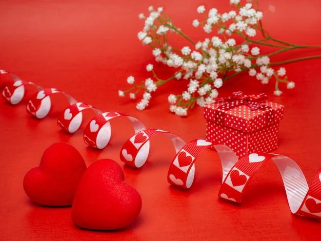 2つのハートと白い花の弓が付いたギフトボックス。バレンタインデー、母の日、または誕生日のお祝いのコンセプト。
