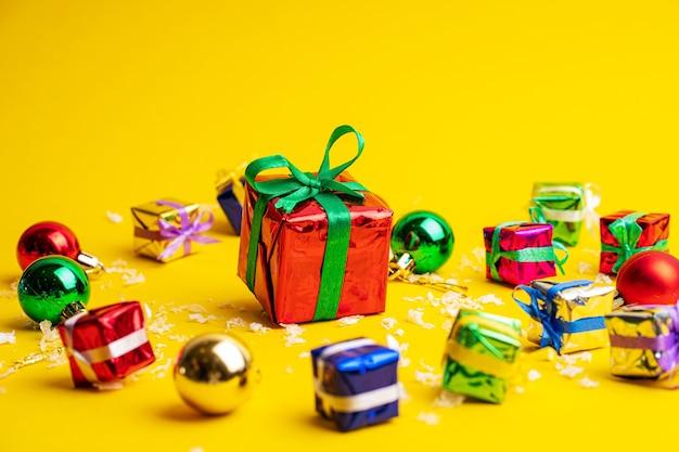 新年の飾りの中に、黄色の背景にクリスマスプレゼントが入ったギフトボックス。