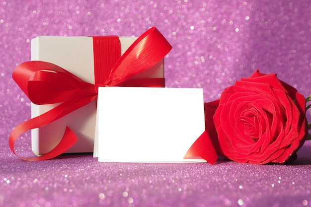 Подарочная коробка с красным бантом и красной розой на фиолетовом блестящем фоне