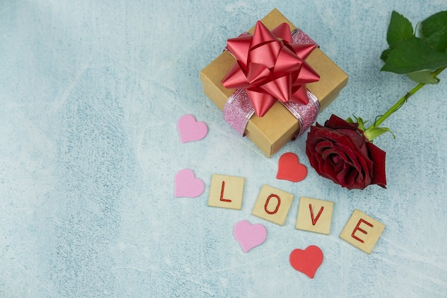 花のバラとボケを背景に赤いリボンが付いたギフトボックス木製の文字が休日のバレンタインのdaを愛する
