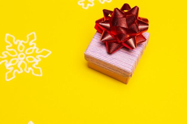 새해 선물을 위한 여유 공간이 있는 노란색 배경에 빨간색 활이 있는 선물 상자