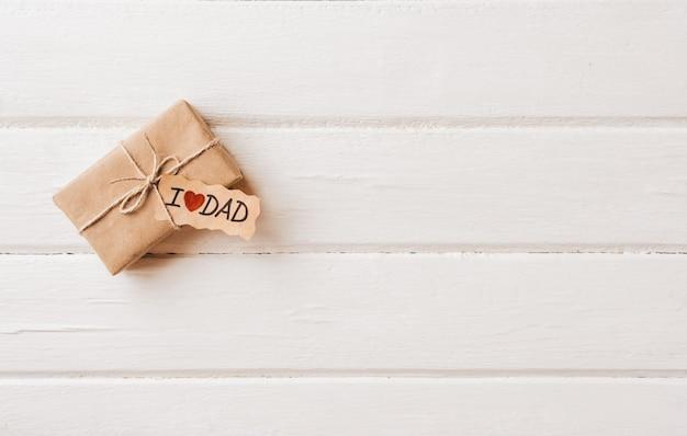 白い木製スペースのタグ付きギフトボックス。父の日や誕生日のコンセプトです。