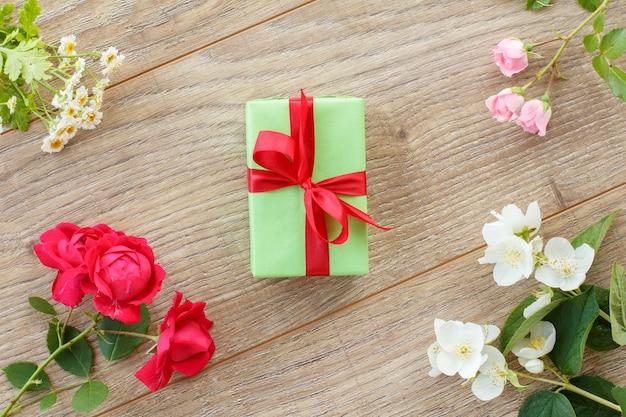 木製の背景に美しいバラ、ジャスミン、カモミールの花が付いたギフトボックス。休日に贈り物をするという概念。上面図。