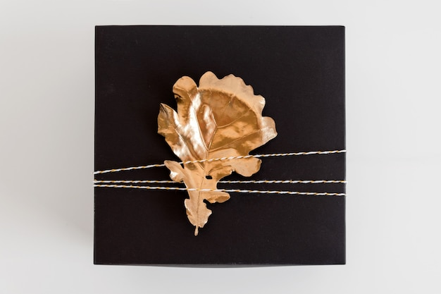 Gift box with autumn golden leaf decoration