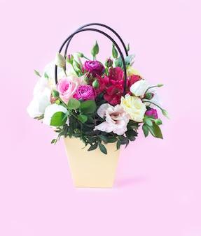 淡いピンクの背景に美しい花の花束(バラ、トルコギキョウ、フリージア)とギフトボックス