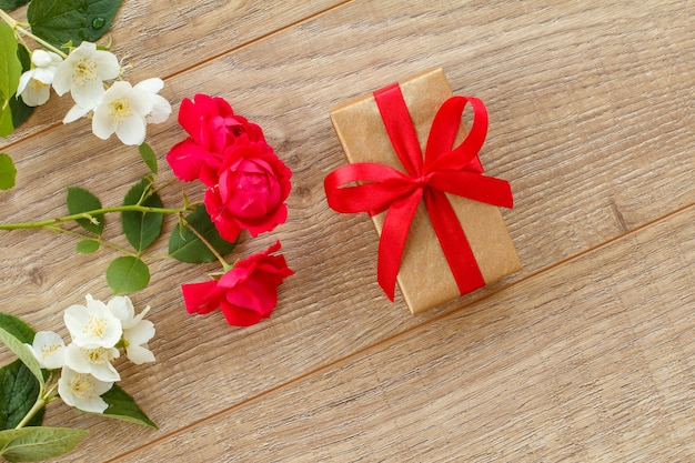 木製の背景に美しいバラとジャスミンの花のギフトボックス。休日に贈り物をするという概念。上面図。