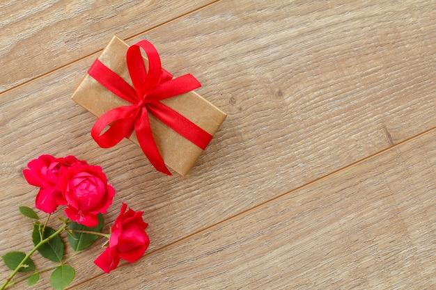 木製の背景に美しいバラの花のギフトボックス。休日に贈り物をするという概念。上面図。