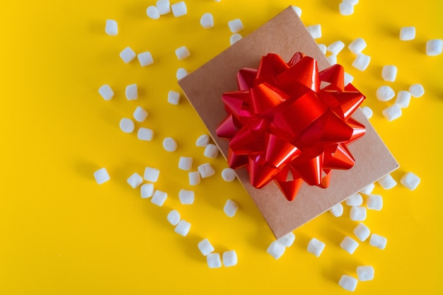 Gift box with big red bow on yellow background. birthday gift, new year, christmas gift box presents, valentines day.