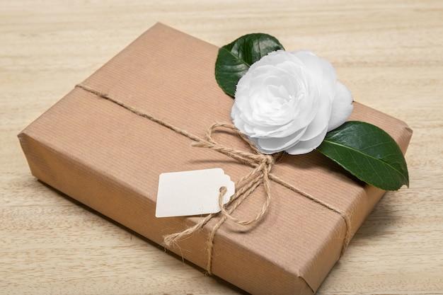 Подарочная коробка с пустой меткой и цветок. празднование или настоящее понятие