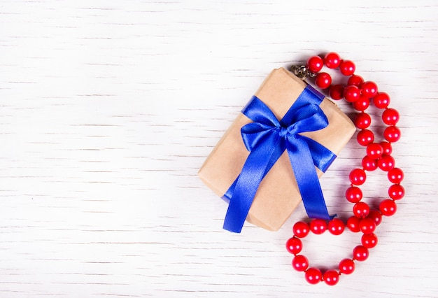 Gift box with blue bow and red coral beads on a white wooden background