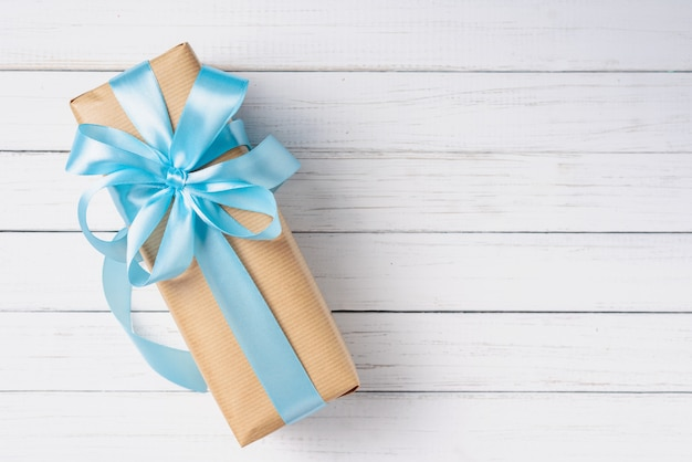 Gift box with blue bow on a white wooden surface with copy space