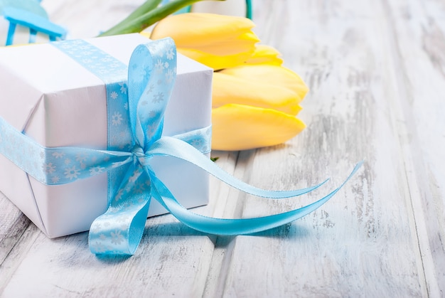 Gift box with a blue ribbon and bouquet of yellow tulips  on a wood