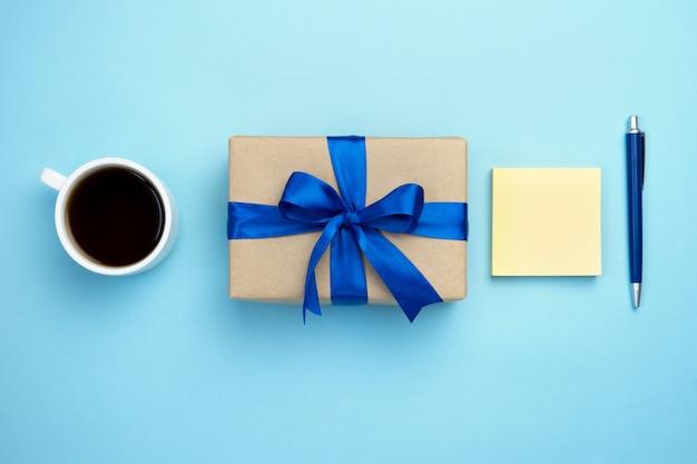 Подарочная коробка с голубой лентой лук чашку кофе и блокнот, изолированных на синем фоне.