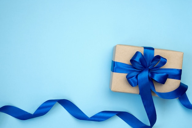 Gift box with blue ribbon bow isolated on blue background.