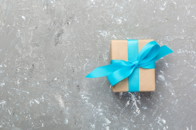 Gift box with blue ribbon on gray background