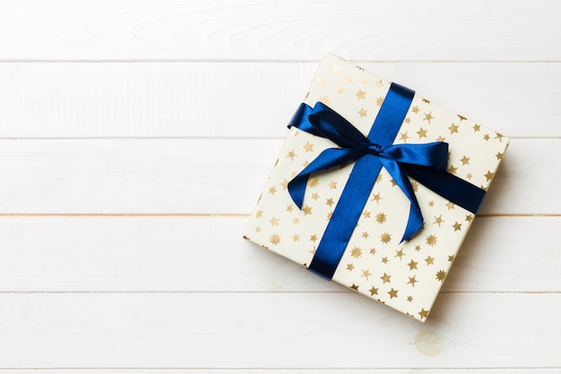 Gift box with blue ribbon on wooden table. flat lay
